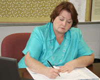 Mulher mais idosa que trabalha em sua mesa Imagem de Stock