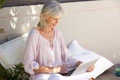 Mulher mais idosa relaxado fora com portátil imagens de stock