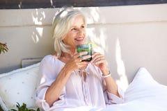Mulher mais idosa relaxado fora do chá bebendo com limão imagem de stock
