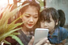 A mulher mais nova asiática e as crianças que olham ao telefone esperto selecionam a imagens de stock royalty free