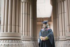 Mulher malaia nova que guarda um certificado do grau ao sorrir em seu dia de graduação foto de stock