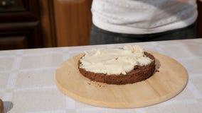 A mulher mancha o creme no bolo de esponja usando a faca, close up das mãos video estoque