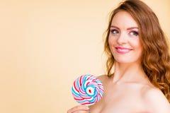 A mulher mantém doces coloridos do pirulito disponivéis imagens de stock