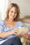 Mulher meados de da idade que lê um livro imagens de stock