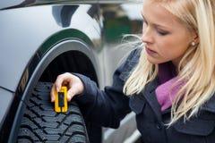 A mulher mede o passo do pneu de um pneu de carro Imagens de Stock