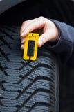 A mulher mede o passo do pneu de um pneu de carro Fotos de Stock
