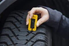 A mulher mede o passo do pneu de um pneu de carro Imagem de Stock Royalty Free