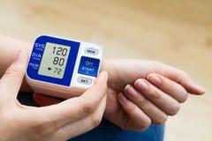 A mulher mede a pressão sanguínea Imagens de Stock Royalty Free