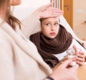 A mulher mede a temperatura da filha Imagens de Stock Royalty Free