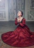 Mulher medieval bonita em rezar vermelho do vestido Foto de Stock Royalty Free