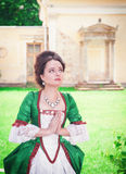 Mulher medieval nova bonita em rezar verde do vestido Imagem de Stock