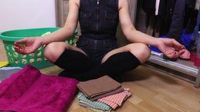 A mulher medita perto do armário vídeos de arquivo