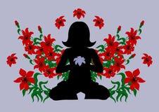 Mulher Meditating cercada com flores Fotografia de Stock Royalty Free