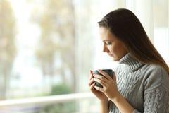 Mulher melancólica triste que guarda uma caneca em casa imagem de stock royalty free