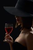 Mulher misteriosa elegante em um chapéu que guarda um vidro do vinho tinto sobre Fotos de Stock Royalty Free