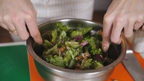 A mulher mistura ingredientes da salada vegetal em uma bacia Close-up de agitar a salada vegetal em uma bacia Misture video estoque
