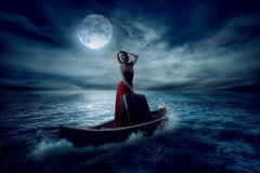 Mulher à moda com a mala de viagem que está em um barco em um meio do oceano Imagens de Stock Royalty Free