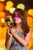 Mulher modelo da beleza que veste a máscara cor-de-rosa do carnaval com uma máscara do ouro em suas mãos Imagem de Stock Royalty Free