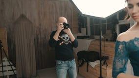 Mulher modelo que levanta para uma fotografia no estúdio vídeos de arquivo