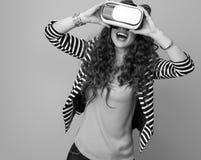 Mulher moderna feliz contra o fundo usando a engrenagem de VR fotos de stock royalty free