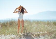 Mulher moderna feliz na posição branca do roupa de banho no litoral fotografia de stock royalty free