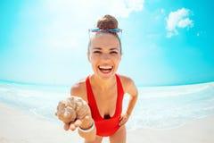 Mulher moderna feliz no roupa de banho vermelho no escudo do mar da exibição da praia fotografia de stock royalty free