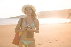 Mulher moderna na moda do moderno do ajuste atrativo que toma fotos com a câmera retro do filme do vintage Fotógrafo do estilo de Foto de Stock Royalty Free