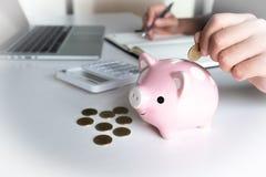 Mulher moderna que põe a moeda no mealheiro cor-de-rosa imagem de stock royalty free