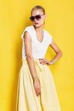 Mulher molhada em óculos de sol cor-de-rosa e na saia amarela imagens de stock