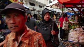 A mulher monta na bicicleta no mercado do alimento em Jakarta, Indonésia video estoque
