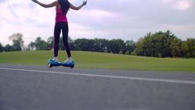 A mulher monta o gyroscooter na estrada do parque Menina que usa o 'trotinette' de equilíbrio do giroscópio do auto filme