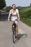 A mulher monta uma bicicleta Fotografia de Stock Royalty Free