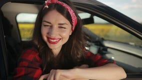 Mulher moreno à moda que inclina-se fora da janela de carro filme