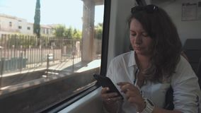 A mulher moreno adulta está conversando pelo smartphone, enviando os sms, sentando-se no trem filme