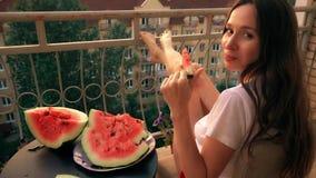 Mulher moreno alegre bonita que come a melancia em um terraço em casa Tempo do prazer da noite do verão Imagens de Stock Royalty Free