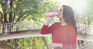 A mulher moreno atrativa anda e bebe o chá de uma caneca thermo cor-de-rosa filme