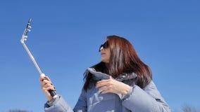 Mulher moreno atrativa nos óculos de sol que fazem o selfie usando o smartphone e a vara ao passar o tempo fora durante vídeos de arquivo