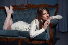Mulher moreno atrativa nova que encontra-se em um sofá Fotos de Stock Royalty Free