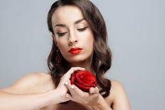 Mulher moreno bonita com batom vermelho nos bordos A menina do close-up com aumentou foto de stock