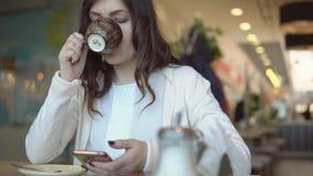 Mulher moreno bonita com o telefone na tabela no café filme