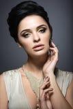 Mulher moreno bonita com pele perfeita, composição do ouro e joia feito a mão Face da beleza Imagens de Stock Royalty Free
