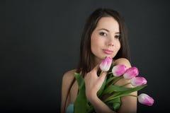 Mulher moreno bonita com tulipas cor-de-rosa Fotos de Stock