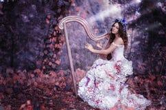 Mulher moreno bonita com uma grinalda da flor em sua cabeça, vestindo um vestido branco que joga a harpa na floresta imagem de stock royalty free