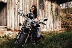 Mulher moreno bonita com uma motocicleta clássica c imagens de stock