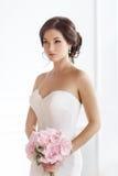 Mulher moreno bonita como a noiva com o ramalhete cor-de-rosa do casamento no branco fotos de stock royalty free