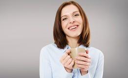 Mulher moreno bonita de riso com a xícara de café no fundo cinzento Copie o espaço fotografia de stock royalty free