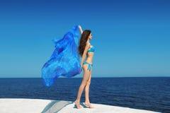 Mulher moreno bonita do modelo do biquini com o tecido de sopro sobre b Imagens de Stock Royalty Free