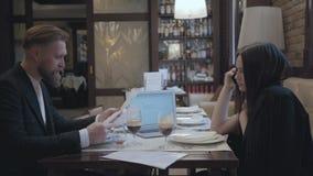 Mulher moreno bonita e homem farpado louro que sentam-se na tabela no funcionamento do café e na cerveja bebendo Portátil, papéis filme