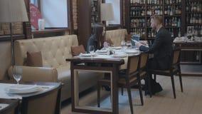 Mulher moreno bonita e homem farpado louro que sentam-se na tabela no funcionamento do caf? O port?til, os pap?is e os vidros est video estoque