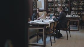Mulher moreno bonita e homem farpado louro que sentam-se na tabela no funcionamento do caf? O port?til, os pap?is e os vidros est vídeos de arquivo